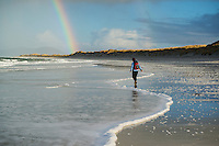 Reflection of woman walking on scenic west coast beach, Berneray, Outer Hebrides, Scotland
