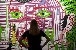 "© Licensed to London News Pictures. 23/03/2018. LONDON, UK. A staff member views ""Douala Tonight"", 2014, by Boris Nzebo (Est. GBP6,000-9,000).  Preview of Modern and Contemporary African Art sale at Sotheby's, New Bond Street.  The auction will take place on 28 March 2018.   Photo credit: Stephen Chung/LNP"