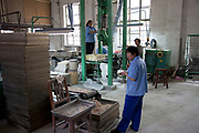 Workers inside a workshop producing art materials. 798 Art Zone or Dashanzi Art District, is a part of Dashanzi in the Chaoyang District of Beijing, China that houses a thriving artistic community, among 50-year old decommissioned military factory buildings of unique architectural style. The area is often called the 798 Art District or Factory 798 although technically, Factory #798 is only one of several structures within a complex formerly known as Joint Factory 718.
