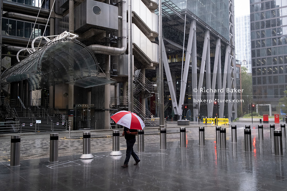 A male City worker carrying a red and white corporate brolly for 'EC3 Brokers', walks through a rain shower outside the lloyds of London building (left) on the corner of Lime Street and Leadenhall, during the Coronavirus pandemic - a time when the normal workforce is still working from home, on 17th August 2020, in London, England.