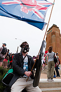 A man in a gas mask holds up a mock flag during the Sack Daniel Andrews Protest in Fawkner Park. Parts of the community are looking to hold the Victorian Premier accountable for the failings of his government that led to more than 800 deaths during the Coronavirus crisis. Victoria has recorded 36 days Covid free as pressure mounts on the Premier Daniel Andrews to relax all remaining restrictions. (Photo by Dave Hewison/Speed Media)