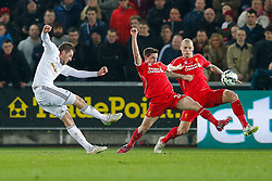 Gylfi Sigurosson of Swansea City shoots as Joe Allen and Martin Skrtel of Liverpool defend - Photo mandatory by-line: Rogan Thomson/JMP - 07966 386802 - 16/03/2015 - SPORT - FOOTBALL - Swansea, Wales — Liberty Stadium - Swansea City v Liverpool - Barclays Premier League.