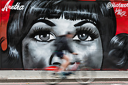 © Licensed to London News Pictures. 19/08/2018. London, UK.  A cyclist passes new street art in Shoreditch, east London, paying tribute to the singer, Aretha Franklin who has died following a battle with pancreatic cancer.  The mural has been created by artist, Jules Muck in collaboration with Global Street Art. Photo credit: Vickie Flores/LNP