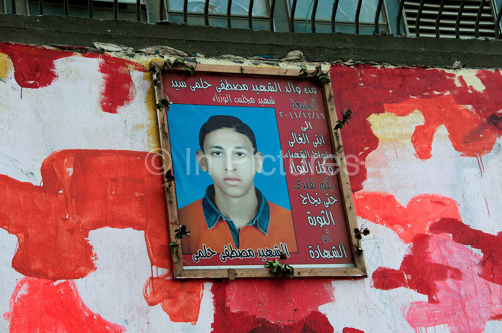 Egypt, Cairo 2014. Mohammed Mansour Street. Revolutionary grafitti. After grafitti was covered up with whitewash activists painted red 'camouflage', reflecting the spilt blood. Also portrait of killed boy.