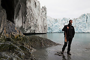 Glaciologist Dariusz Ignatiuk stands with a rifle (against polar bears) below the terminus of Hansbreen glacier, Hornsund, Svalbard.