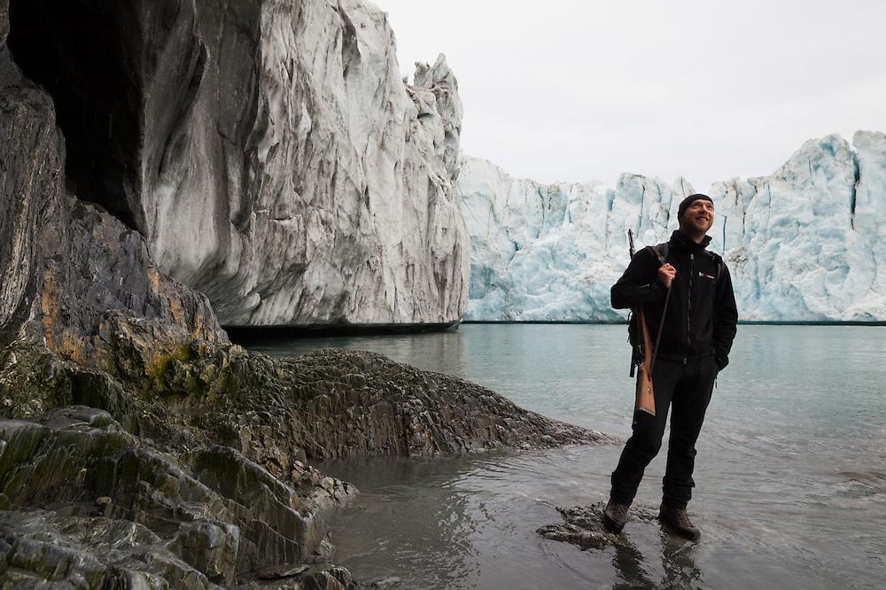 Glaciologist Dariusz Ignatiuk stands with a rifle (against polar bears) below the terminus of Hansbreen glacier, Hornsund, Svalbard.