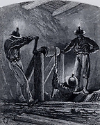 A Cornish winze shaft, used for exploration.  A man attached to a rope is being lowered down the shaft by a simple windlass. For light the men have nothing more than bare candles stuck in their hats. Cornwall, England. From 'Underground Life; or, Mines and Miners' by Louis Simonin (London, 1869). Wood engraving.