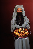 Woman in traditional Moroccan dress and veil serves a local dish. Photo by Terry Fincher