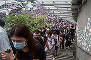 Protesters try to escape tear gas beside the Central Government Offices, during a protest against a proposed extradition law in Hong Kong, SAR China, on Wednesday, June 12, 2019. Hong Kong's legislative chief postponed the debate on legislation that would allow extraditions to China after thousands of protesters converged outside the chamber demanding the government to withdraw the bill. Photo by Suzanne Lee/PANOS