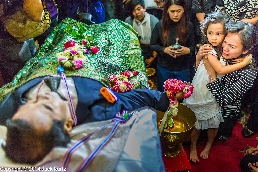 27 JANUARY 2014 - BANGKOK, THAILAND:  A woman and her daughter participate in the bathing rites for anti-government leader Suthin Taratin at Wat Sommanat Rajavaravihara in Bangkok. In Thai tradition, after death a bathing ceremony takes place in which relatives and friends pour water over one hand of the deceased. Suthin was a core leader of the People's Democratic Force to Overthrow Thaksinism (Pefot), one of several organizations leading protests against the elected government of Thai Prime Minister Yingluck Shinawatra. He was murdered Sunday, Jan. 28, while he was leading a rally to prevent voters from reaching a polling center in the Bang Na district of Bangkok.    PHOTO BY JACK KURTZ