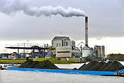 Nederland, Nijmegen, 25-11-2015Elektriciteitscentrale van Electrabel, onderdeel van GDF SUEZ Energie Nederland. Het is een kolengestookte centrale, en staat op de nominatie om gesloten te worden vanwege ouderdom, stroomoverschot en milieuakkoord. Er worden ook biomassa en houtsnippers verstookt. Op de voorgrond een binnenvaartschip geladen met kolen, kolengruis, brandstof voor dit soort centrales, op de Waal.Foto: Flip Franssen/HH
