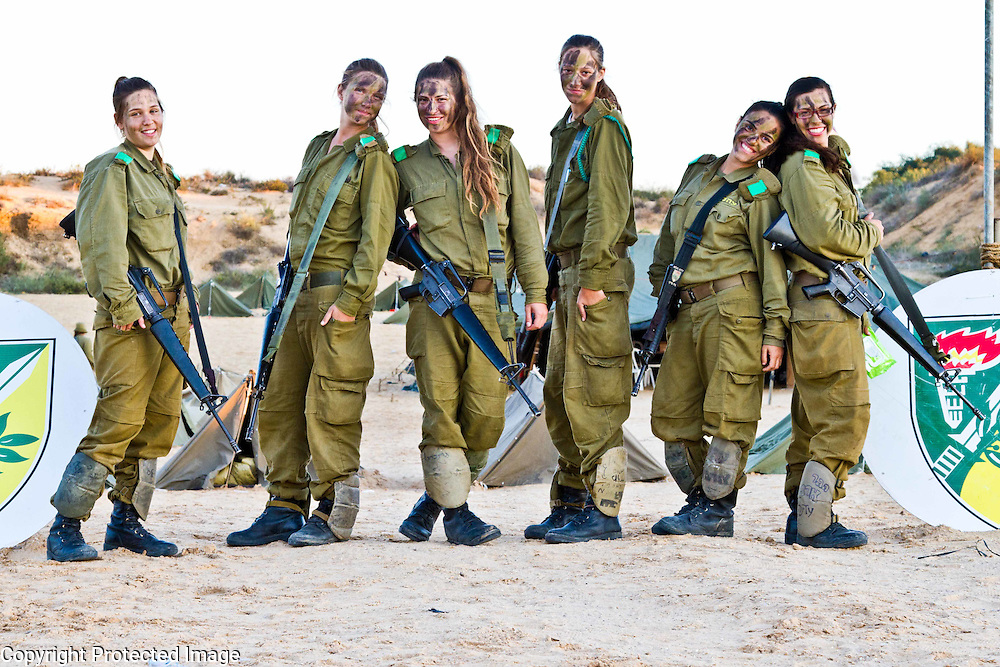 FIve Israeli soldiers with rifles and face paint stand at the entrance of their field camp, near Palmachim, Israel. Photography by Debbie Zimelman, Modiin, Israel. Specialization in documentary photography
