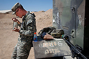 "U.S. Army officer Curtis Newcomer eats chili mac, his favorite MRE, at lunch time at the National Training Center at Fort Irwin in California's Mojave Desert. (From the book What I Eat: Around the World in 80 Diets.) The caloric value of his day's worth of food in the month of September was 4,000 kcals. He is 20; 6'5"" and 195 pounds. His weapon is fitted with a laser that interacts with receivers worn by all of the soldiers and actors in the training exercise, regardless of duty, rank, or location in the training theater. At left: After the second of three mock battles of the day, Iraqis and Americans playing soldiers, victims, and insurgents relax together in the shade until the next 20 minutes of choreographed crisis. MODEL RELEASED."
