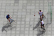"""Boys play bicycle football in a square in Ghent - they """"kick"""" the ball with the front tyre of their bikes, but can use their hands to prevent the ball from going into the goal net"""