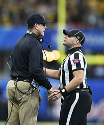 Michigan Wolverines head coach Jim Harbaugh talks to the official during a replay review during the Chick-fil-A Bowl Game at  the Mercedes-Benz Stadium, Saturday, December 29, 2018, in Atlanta. ( AJ Reynolds via Abell Images for Chick-fil-A Kickoff)