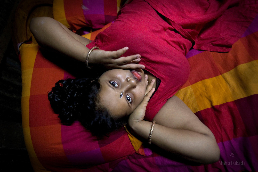 Sex worker Munnie, 15, lies down on her bed at brothel in Tangail, Bangladesh.