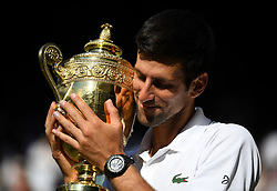 Novak Djokovic with the trophy after winning the Gentlemen's singles final on day thirteen of the Wimbledon Championships at the All England Lawn Tennis and Croquet Club, Wimbledon.