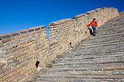 Chinese boy walking up steps of the Great Wall of China at Mutianyu, north of Beijing, China