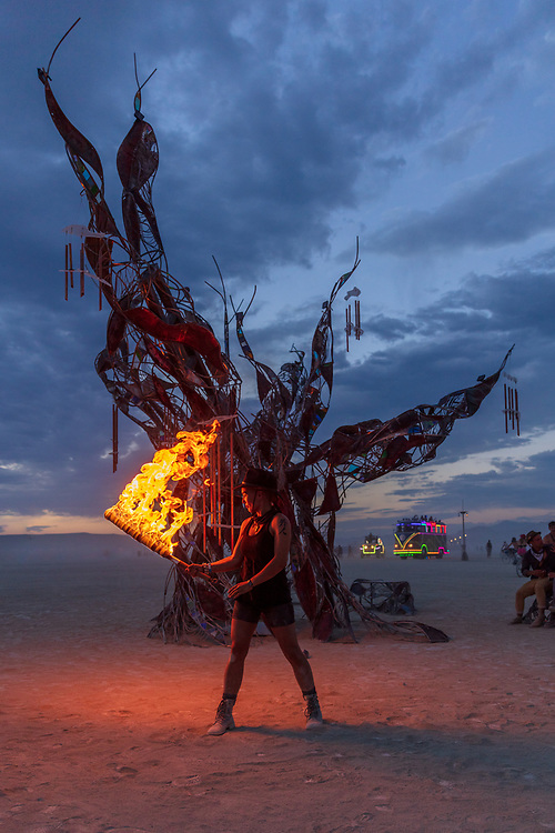 Firedancer at Methuselah is a 20′ metal sculpture of the world's oldest tree. The tree's bark is steel, patinated to blue, brown & white, and seams of glass reveal propane flames within the trunk, reflected in a mirror below. The tree's roots form benches on which Burners can congregate. Ancestry and evolution are central themes for our work, whose namesake's rings and branches bore witness to the entire span of recorded human history. Great trees gave their limbs and leaves as axles, paper, bows, hulls and roofs, and held space and time for our ancestors' radical rituals. Black Rock City contains many altars of dance and ecstasy, and many more of learning and relaxation, but the city provides comparatively few spaces for contemplation and remembrance. Circular spaces, lone trees and eternal flames are all strong ritualistic symbols and joining them in Methuselah helps to dislocate Participants from the frenzy of present day time and re-anchors them in the still time of mythology. URL: http://www.graydavidson.com/art/methuselah Contact: msnaiman12@gmail.com