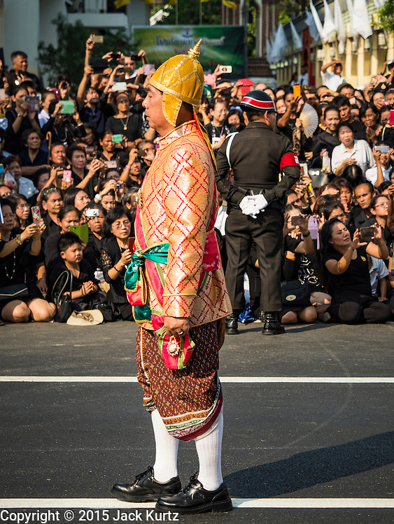 16 DECEMBER 2015 - BANGKOK, THAILAND:  A member of an honor guard in traditional Thai dress walks past the crowd during the funeral procession for Somdet Phra Nyanasamvara, who headed Thailand's order of Buddhist monks for more than two decades and was known as the Supreme Patriarch. The Patriarch died in 2013. He was ordained as a Buddhist monk in 1933 and appointed as the Supreme Patriarch in 1989. He was the spiritual advisor to Bhumibol Adulyadej, the King of Thailand when the King served as a monk in 1956. Tens of thousands of people lined the streets during the procession to pray for the Patriarch.    PHOTO BY JACK KURTZ
