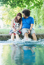 Happy couple sitting with feet in water at Eisbach River
