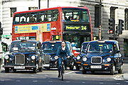 Biker in front of heavy traffic in Trafalgar Square, downtown London city centre, England, United Kingdom