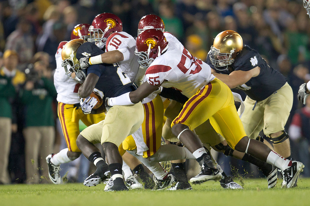 Notre Dame running back Cierre Wood (#20) is tackled by USC defenders led by USC linebacker Hayes Pullard (#10) during second quarter of NCAA football game between Notre Dame and USC.  The USC Trojans defeated the Notre Dame Fighting Irish 31-17 in game at Notre Dame Stadium in South Bend, Indiana.