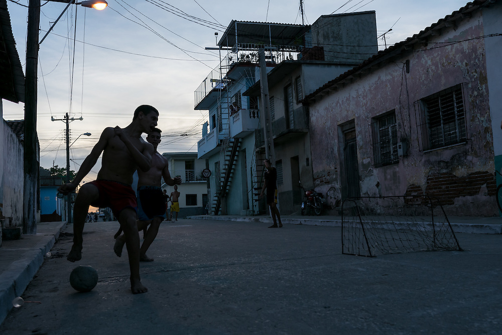 Youngsters playing football on street in Santi Spiritus, Cuba.