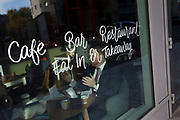 A businessman gestures with his face partially-obscured by the writing in a cafe window, on 13th November 2017, in London, England.