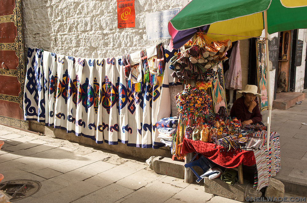 A vendor sells Tibetan dorr coverings and other souvenirs on the Barkor in Lhasa, Tibet.