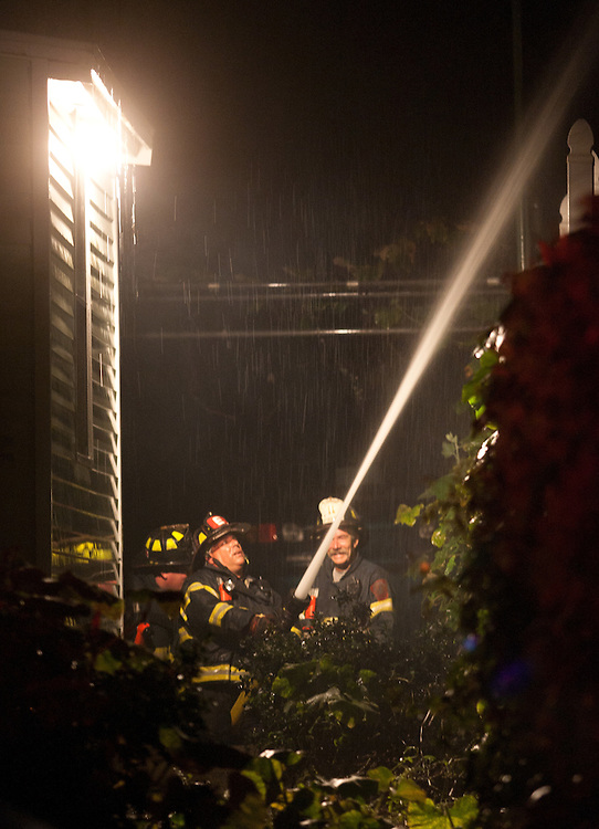 Quincy, MA 10/09/2011.Quincy Fire Department firefighters operate a hose line at the scene of a 2 alarm house fire at 44 Penn St. on Sunday night..Alex Jones / www.alexjonesphoto.com