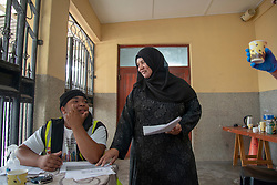 """Max Swartz Amanensure and Shanaaz Jacobs share a light moment at the Masjidus Sabr mosque that has become headquarters for a joint, interfaith, Parkwood Covid-19 feeding response team. Volunteers today delivered bread to the community of Parkwood, a subburb of Cape Town, located on the Cape Flats, Monday, April 20, 2020. The majority of the people who live here are unemployed during """"normal"""" circumstances. And as South Africa is now in lockdown due to the Coronavirus, many of those who had jobs have also lost their income. So many people are starving. The feeding scheme is a joint community effort, paid for solely by donations from the public to feed more than 3,000 households. The group is also receiving transportation support by The South African Red Cross Society. PHOTO: EVA-LOTTA JANSSON"""