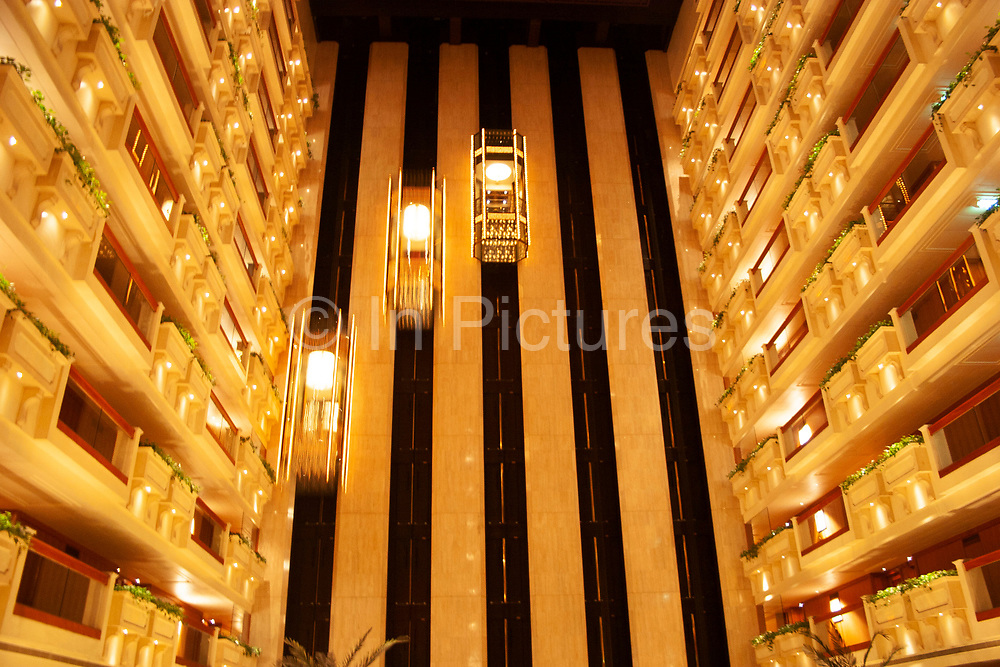 Elevators and balconies in the atrium at Hong Kong's famous Royal Garden Hotel in Hong Kong, China. Situated on the Kowloon side of Hong Kong Harbour, this architectural classic interior draws many people to the bar and restaurant area just to experience the space or to travel up and down in the elevators. Centrally based in Tsim Sha Sui east shopping district.