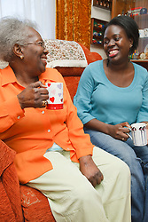 Daughter and mother having a laugh over a cup of tea.