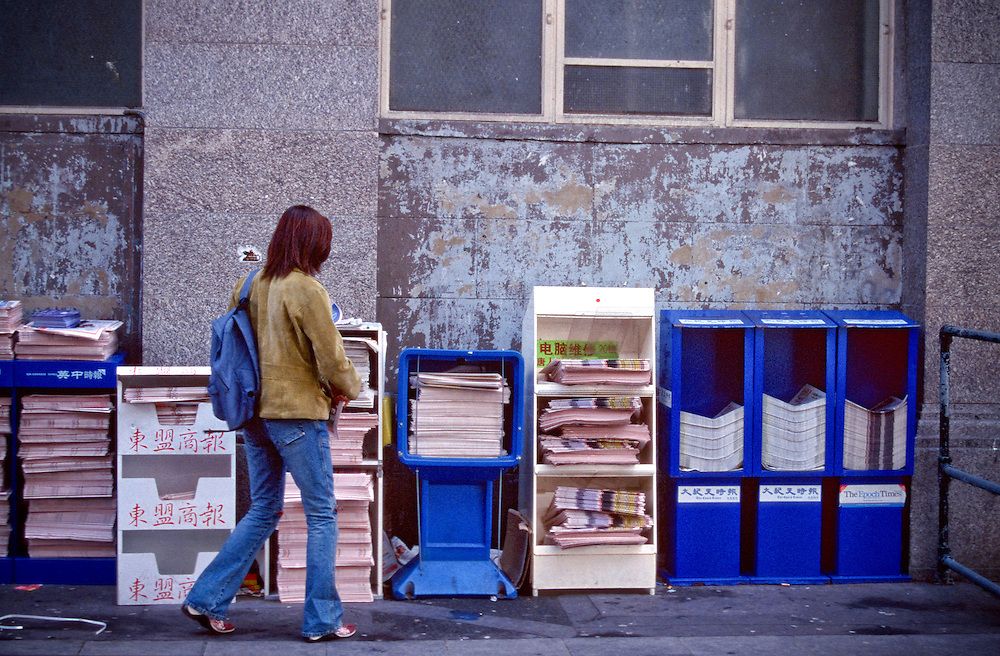 A woman picks up one of the free Chinese newspapers on offer in Chinatown, London.