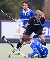 UTRECHT- Hockey -  HGC aanvoerder Floris van der Linden in duel met de op de grond liggende Boet Phijffer van Kampong tijdens de hoofdklasse competitiewedstrijd tussen de mannen van Kampong en HGC (2-1). Op de achtergrond Robbert Kemperman van Kampong. COPYRIGHT KOEN SUYK