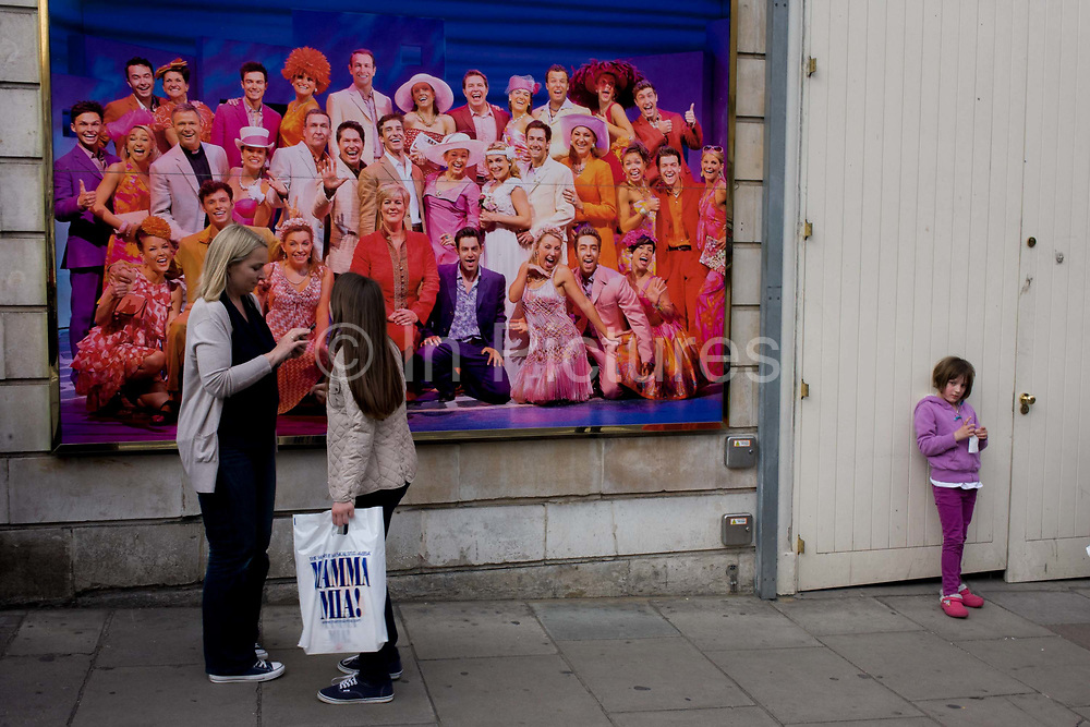 Older woman and younger girls in front of poster for Mamma Mia musical in London's West End. Wearing a similar purple to the show's poster, a young girl stands aside from the others, one holding a plastic bag with the production's title. The mother fiddles with a camera or smartphone before they all go into the Novello Theatre in London's Drury Lane to watch the spectacular. Mamma Mia is named after Swedish 70s pop group Abba's hit song which has become a massive film and stage show.