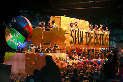 12 Feb 2015. New Orleans, Louisiana.<br /> Mardi Gras. The 'Spin the bottle' float, parodying the local pawer struggle between Rita and Gayle Benson of the Saints and Pelicans makes its way along Magazine Street  with the The Krewe of Muses. <br /> Photo; Charlie Varley/varleypix.com