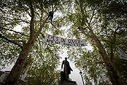 "Extinction Rebellion demonstrators with a banner reading ""Eyes on Government IN-Action' protest in the trees above the Robert Peel statue in Parliament Square outside the House of Commons for the climate and ecological emergency.  Westminster London, United Kingdom. Extinction Rebellion is a political movement with the main aim to avert climate breakdown, minimise human extinction and stop ecological collapse using non violent resistance."