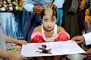 Family members shave the boys head and the hair is caught in a white cloth held by their parents at a Shinbyu Novice Ceremony on 28th March 2016 in the Intha ethnic minority village of Paya Ny in Kayah State, Myanmar. In Myanmar, it is customary for boys to enter the monastery as a Buddhist novice between the age of ten and 20 years old although they can be as young as four, for at least one week. During the ceremony, which lasts two or sometimes three days, the boys are dressed and made-up to be a prince and paraded through the village before being ordained as novice monks.  head and the hair is caught in a white cloth held by their parents. at a Shinbyu Novice Ceremony on 28th March 2016 in the Intha ethnic minority village of Paya Ny in Kayah State, Myanmar. In Myanmar, it is customary for boys to enter the monastery as a Buddhist novice between the age of ten and 20 years old although they can be as young as four, for at least one week. During the ceremony, which lasts two or sometimes three days, the boys are dressed and made-up to be a prince and paraded through the village before being ordained as novice monks.