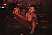 YANOMAMI INDIANS. South America, Brazil, Amazon. Children in hammock, iving inside Molaca or Shabono traditional dwelling. Yanomami indians, a primitive tribe, living in the tropical rainforest, in communal traditional molaca dwellings. They are huntergatherers passing on their traditions and skills  from generation to generation. They are the guardians of their forest and its fragile ecosystem. Their lifestyle and their lands diminish every year in the face of encroaching deforestation, forest fires, campesinos who slash and burn primary rainforest, from cattle ranching, commercial plantations, gold and diamond mines.