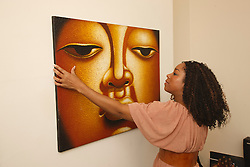 Young black woman hanging up a painting..