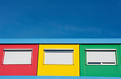 Three modern colorful steel huts with windows and shutters containing small school in Amsterdam The Netherlands