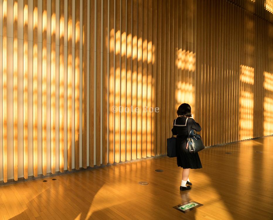 Japanese school girl in uniform walking through a brightly sun lit hall