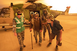 December 21, 2019, Nowra, New South Wales, Australia: FRANK DELANEY and WARREN USHER of Yalwal, is assisted from an 808 Squadron MRH90 Military Support Helicopter after being evacuated from his remote rural property to the east of the Moreton National Park and in the direct fire front of the Tianjara Fire burning north through ten thousand hectares of national park and bushland. (Credit Image: © Kelvin Hockey/Royal Australian Navy via ZUMA Wire)
