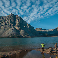 Photographers shoot dramatic clouds soaring over Crowfoot Mountain and Bow Lake in Banff National Park, Alberta, Canada. On the right is Mount Thompson.