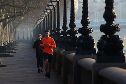 London, February 24th 2016. Runners jog beside the River Thames on Cheyne Walk as the sun rises on a chilly but clear London morning. ///FOR LICENCING CONTACT: paul@pauldaveycreative.co.uk TEL:+44 (0) 7966 016 296 or +44 (0) 20 8969 6875. ©2015 Paul R Davey. All rights reserved.
