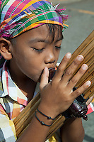 Lao Flute Player at Chatuchak - The khene is a mouth organ of Lao origin whose pipes, which are usually made of bamboo into which air is blown, creating a sound similar to that of the violin. Similar instruments date back to the Bronze Age of Southeast Asia.  According to Lao legend, the khene was created by a woman who was trying to reproduce the sound of the garawek bird which she heard while on a walk one day. The journey was long and difficult, so she decided to invent an instrument that would bring the sound to her.
