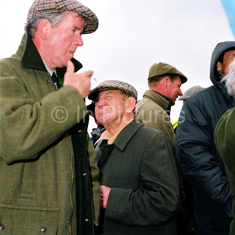 Spectator wearing tweed jackets and flat caps standing by the betting kiosks at the Tiverton Staghounds point-to-point steeplechases at Bratton Down, Barnstaple, Devon, UK. Fundraiser for the Devon and Somerset Staghounds.