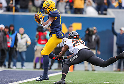 Nov 23, 2019; Morgantown, WV, USA; West Virginia Mountaineers wide receiver George Campbell (15) catches a touchdown pass with Oklahoma State Cowboys safety Jarrick Bernard (24) attempting to tackle during the second quarter at Mountaineer Field at Milan Puskar Stadium. Mandatory Credit: Ben Queen-USA TODAY Sports